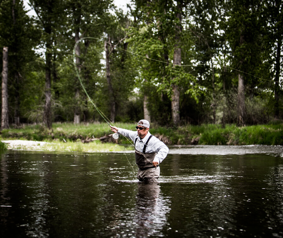 Person fly fishing in river.